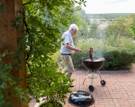senior man grilling ribs on front porch