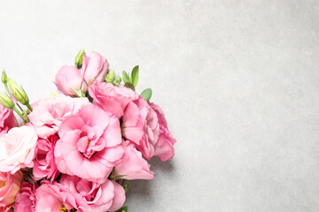 Beautiful bouquet of pink Eustoma flowers on light grey background, top view. Space for text