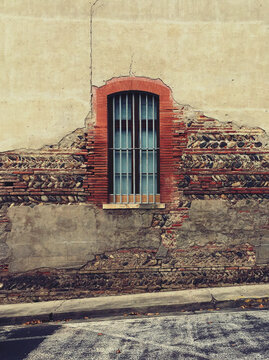 Old window surrounded in bricks in an old destroyed wall. Village ambiance. Carbonne, France.