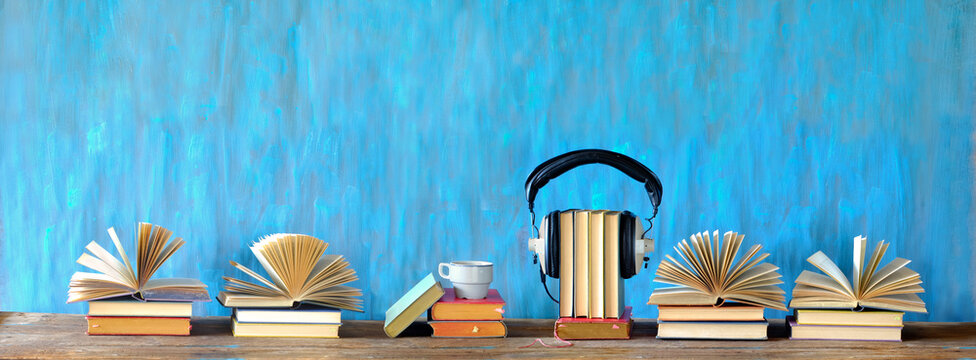audio book concept with open books, cup of coffee, and vintage headphones, panoramic, good copy space