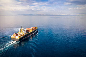 Aerial view of a loaded cargo container ship traveling over calm ocean towards the next commercial port