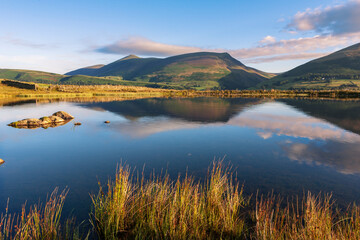 Tewet Tarn and beyond, across the Greta Valley, Lonscale Fell and Skiddaw, reflected in the lake: near Keswick, Lake District National Park, Cumbria, England, UK