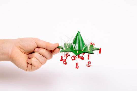 Step by step instruction how to make Christmas tree. Make a cone imitating the top from paper and glue it to a small star. Fasten the thread with a drop of glue and cut the excess. Hand holds craft