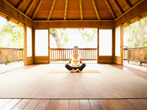 Woman sitting in lotus position on floor of yoga and meditation pagoda at a luxury resort