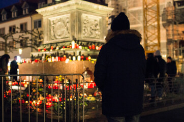 Obraz Hanau, Germany - February 20 2020: Flowers and Candles at the Hanau shooting site as a remembrance to the victims. Right extremism. Terror attack. - fototapety do salonu
