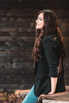 Side view portrait of a beautiful brunette girl in black blazer