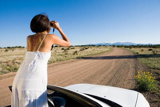 Native American woman in sun dress driving a white convertible sports car on desert dirt road