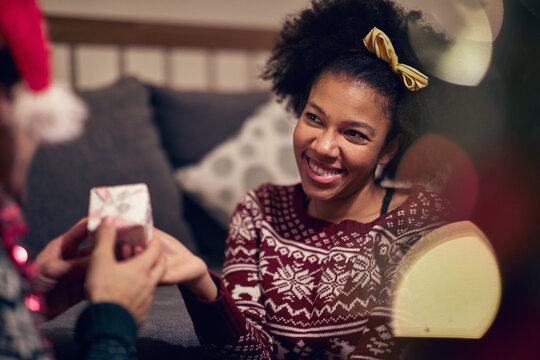 Cheerful teenage girl reciving present; Happy family moments concept