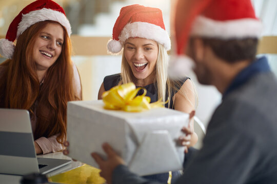 pleasantly surprised female colleague taking wrapped present for christmas wearing santa hat
