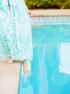 Caucasian woman dipping foot into swimming pool