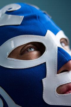 Close up of blue eyed man wearing  a blue wrestling mask