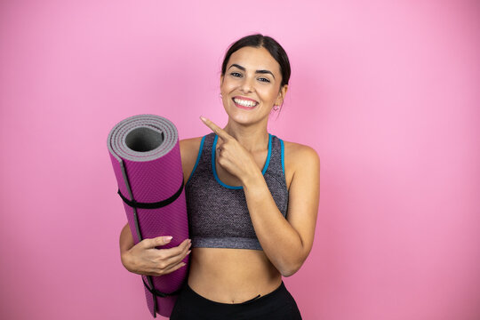 Young beautiful woman wearing sportswear over isolated pink background pointing finger up to the side surprised. Holding a splinter in her hand.