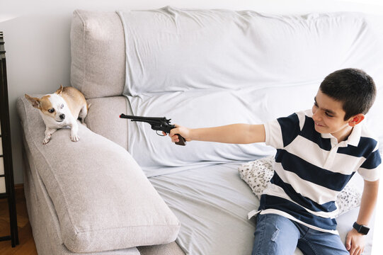 Caucasian boy pointing his toy gun to his dog while sitting on a bed