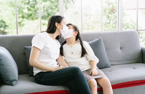 Portrait of young Asian mother and little daughter sitting on sofa are happy to wearing medical mask and kissing mother on cheek in living room at home.Coronavirus, Covid-19, outbreak concept.