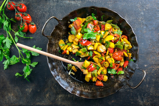 Traditional French ratatouille with vegetable and potatoes offered as top view in a rustic wrough-iron skillet with copy space