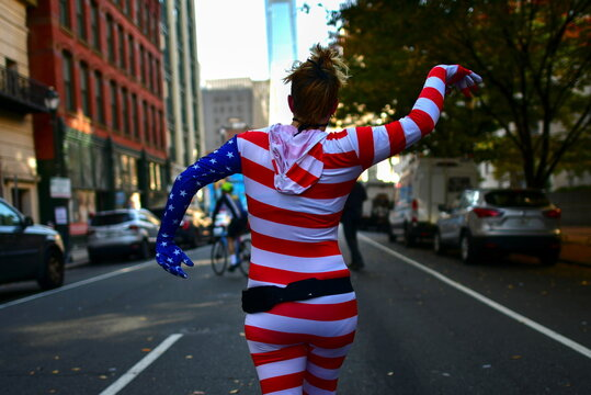 A woman wearing a patriotic bodysuit dances in the street, in Philadelphia