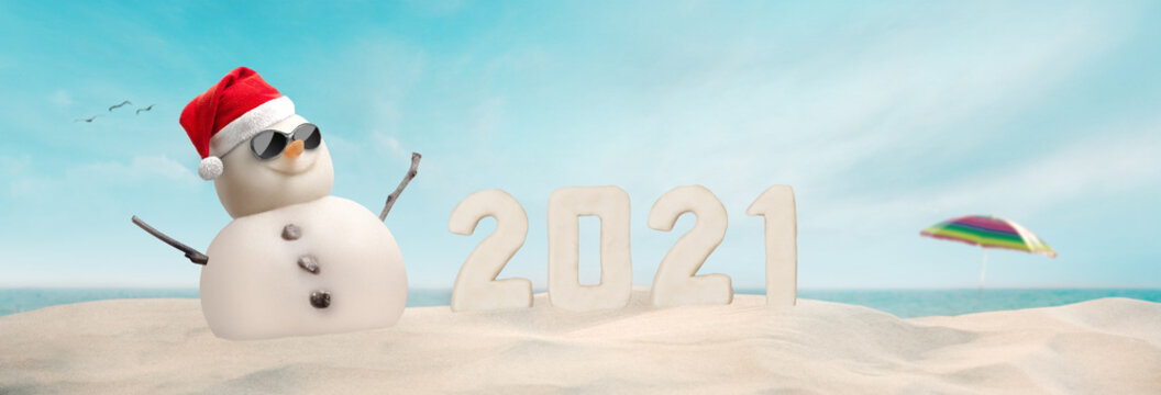 concept - happy sand snowman in sunglasses and Santa hat with number 2021 on sunny Christmas day afternoon