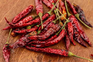 chili pepper hot pod red heap on wooden table seasoning background