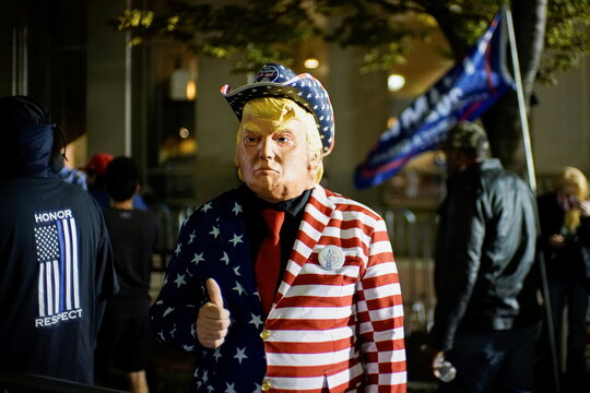 A supporter of U.S. President Donald Trump dressed with the U.S. flag colors and a mask depicting Trump gives a thumbs up as votes continue to be counted following the 2020 U.S. presidential election, in Philadelphia, Pennsylvania