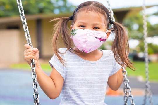 Young student child wearing a mask playing at the park playground.