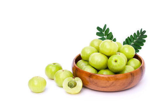 Closeup Indian gooseberry fruits ( phyllanthus emblica, amla ) in wooden bowl with green leaf and slice isolated on white background.