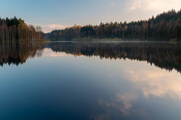 Czech autumn foliage trees landscape reflected in Rimov dam with misty fog