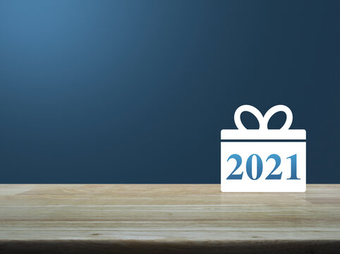 Gift box happy new year 2021 flat icon on wooden table over light blue gradient background, Business shop online concept