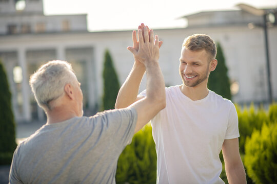 Young brown-haired male and grey-haired male giving high five, smiling