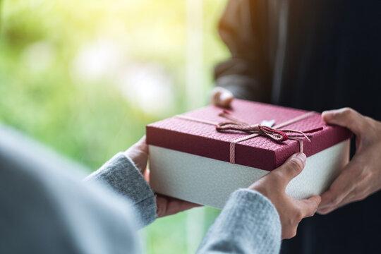 Closeup image of a man giving a woman a gift box