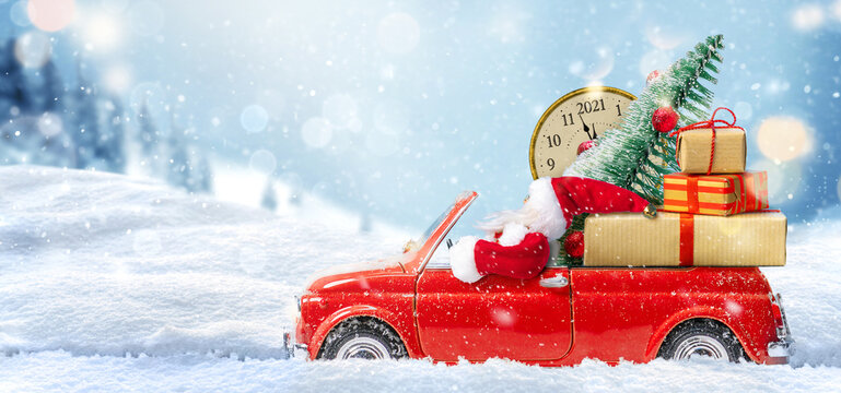 Christmas is coming. Santa Claus in red toy car delivering gifts for New Year 2021