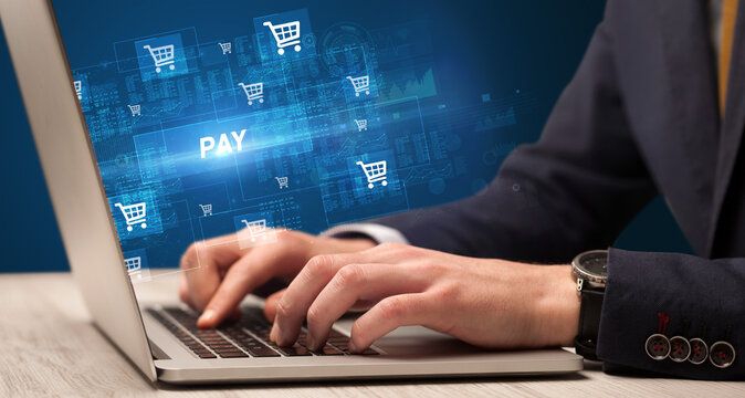Businessman working on laptop with PAY inscription, online shopping concept