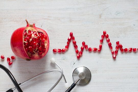 Fruit pomegranate, stethoscope and ECG cardiogram from pomegranate seeds, healthy heart diet concept abstract