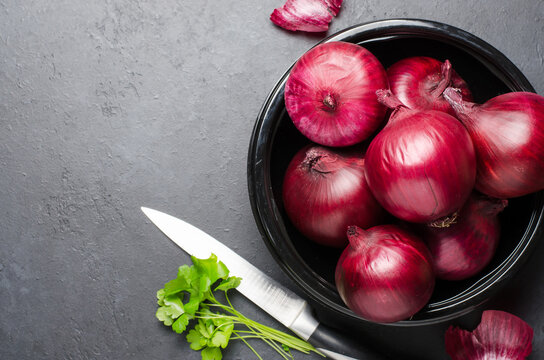 Red ripe onion in a black plate. Dark background. Copy space