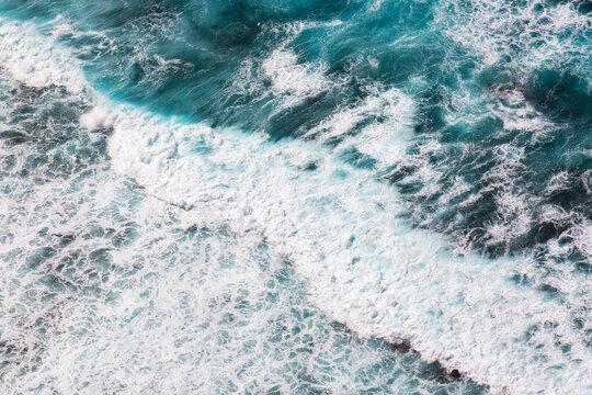 Aerial view of waves in clear ocean at Kelingking beach, Nusa Penida, Bali, Indonesia