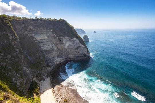 Steep cliffs with crystal clear ocean and waves at Kelingking beach, Nusa Penida, Bali, Indonesia