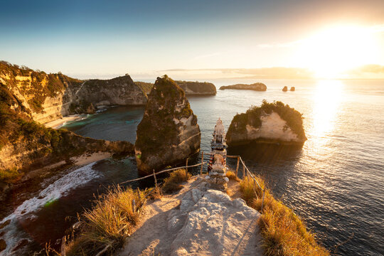 Sunrise over steep cliffs and crystal clear ocean with small temple in foreground at Thousand Islands viewpoint, Nusa Penida, Bali, Indonesia