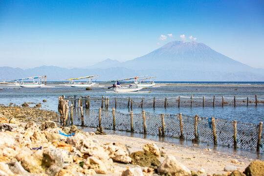 Seaweed farm in the ocean with fishin boats and Gunung Agung vulcano in the background at Nusa Penida, Bali, Indonesia