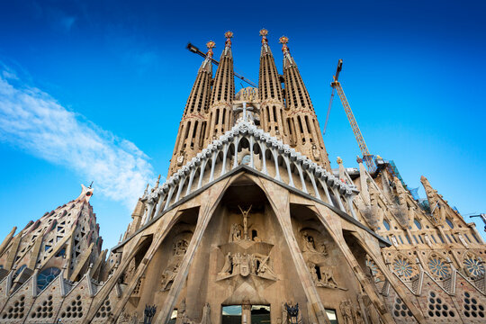 Sagrada Familia church (Gaudi) in Barcelona with blue sky and construction cranes in background