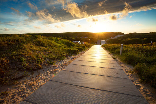 Path through sand dunes during sunset at the island of Texel, The Netherlands