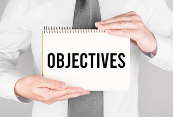 Businessman with notebook with text Objectives