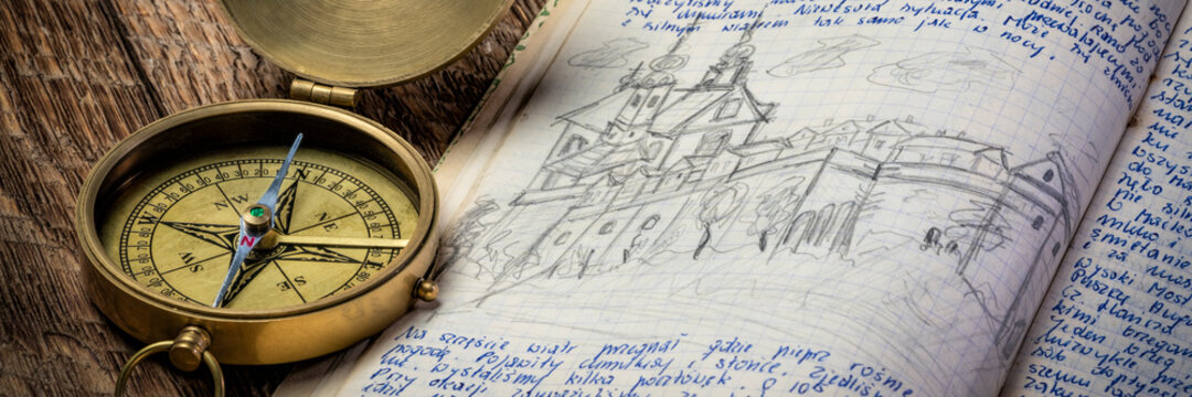 Vintage brass compass and old travel journal with handwriting and pencil sketches (property release attached), travel concept.