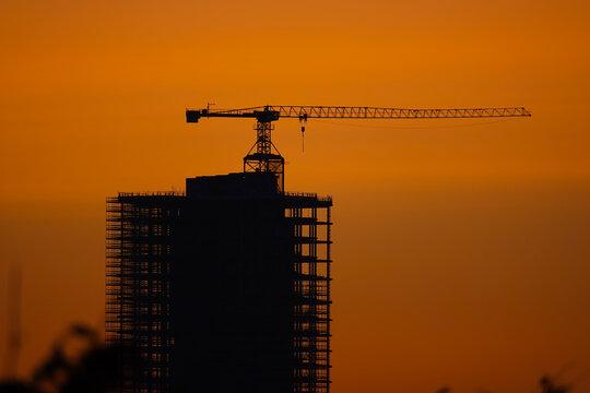 Hochhaus mit Baukran auf dem Dach bei Sonnenuntergang