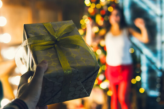 a man's hand holds a gift box with bow and gives a joyful girl on Christmas eve. couple gift