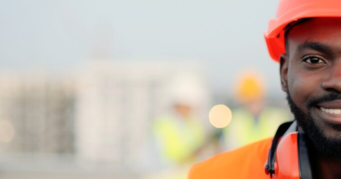 Portrait of half face of handsome African American young man in casque and headphones looking at camera at construction site and smiling. Close up of happy male builder at building. Constructing.