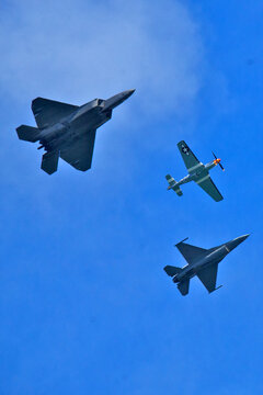 Three generations of fighter planes fly in formation,  F-22 Raptor,  P-51 Mustang, and the  F-16 Fighting Falcon