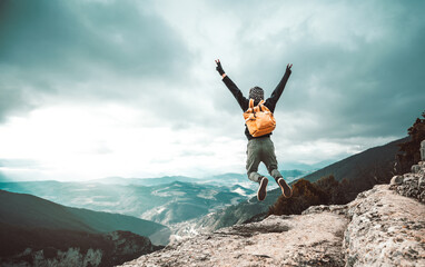 Hiker jumping on the top of the mountain - Successful man raising arms raising arms up.