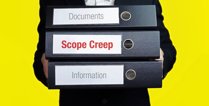 Scope Creep. Man carries stack of folders. File folders with text label. Background yellow.
