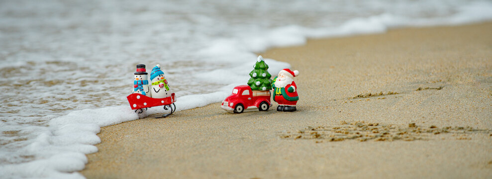 Toy Santa Claus snowman on sea, concept for travel destinations in hot tourist countries.