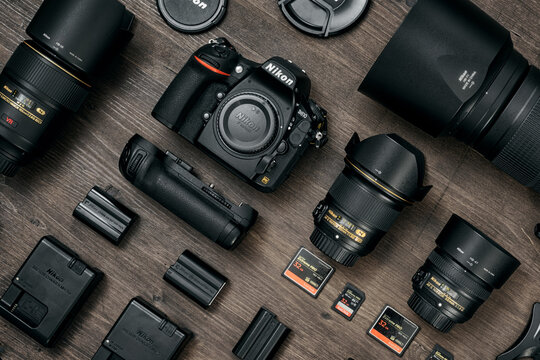 Cagliari, Italy 06/1/2020; Top view of Nikon professional Dslr  equipment, work space photographer with two Nikon D810 and Sandisk Memory Cards on wooden surface.