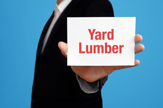Yard Lumber. Businessman in suit showing business card with text. Man isolated on blue background